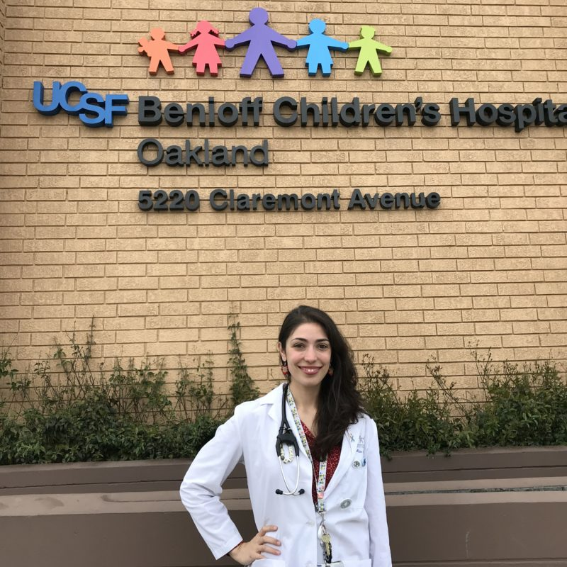 (Doctor in white coat smiling in front of Benioff Children's Hospital)