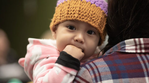 (Baby with hand in her mouth stares over her mother's shoulder)