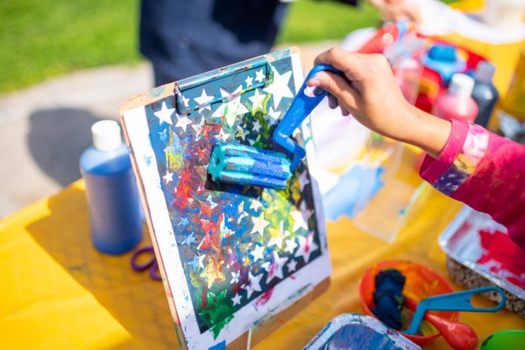 Image of child's hand painting stars