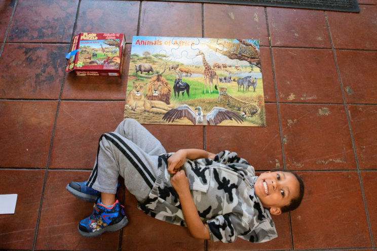 boy lying on floor with puzzle