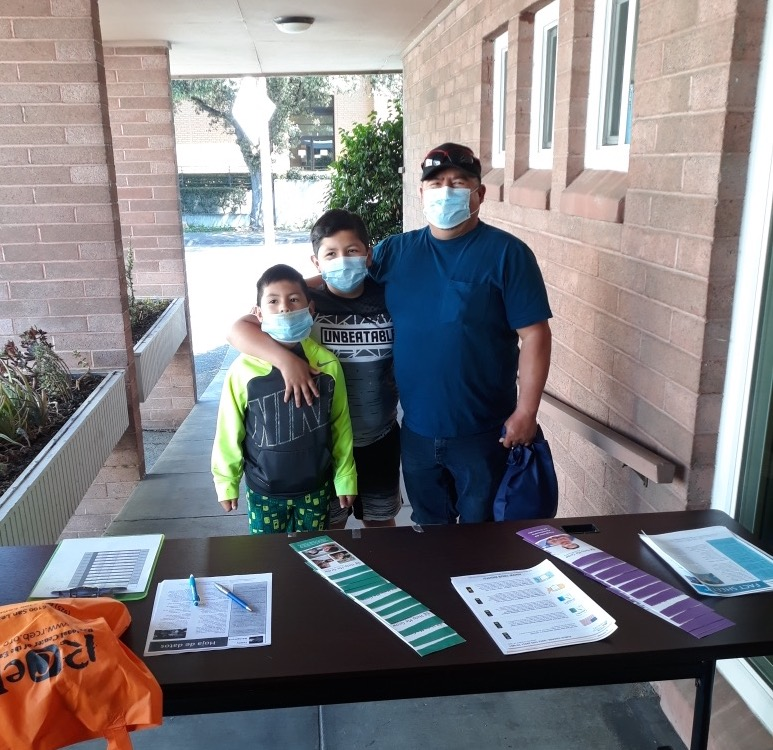 mother father and son with masks on at outreach table