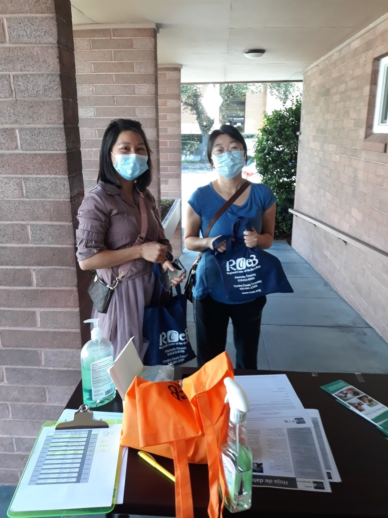 picture of two women with bags of personal protective equipment