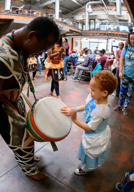 Man with an African drum leans down as a young child beats the drum